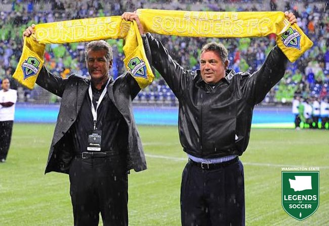 Tacoma and NASL Sounders legends Jeff Stock, left, and Mark Peterson raise their golden scarves prior to the first MLS league match vs. Portland. (Sounders FC photo)