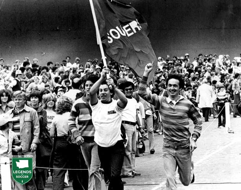 Teddy Mitalis of Seattle carries the Sounders flag as the Sounders fans gather for Soccer Bowl '77.